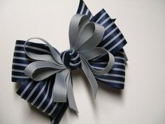 Hello and welcome,   This boutique style bow is made of 2 1/4 inch quality gray grosgrain ribbon, followed by a layer of 1 1/2 inch wide specialty tuxedo blue and gray striped ribbon. I have then added fun thinner gray ribbon and a matching striped knot in the center. This bow measures approx. 4 inches in size..    Please Note--- I take great care to adequately secure novelty pieces onto my bows. As a safety precaution, I recommended that those bows with novelty pieces be worn under adult…