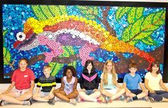Morgan Phillips, Ayden Wilhelm, Sophia Thomas, Olivia Pooley, Erica Wilson, Maddock Stimpson and Madeline Phillips help display the scale of the mural outside art teacher Jan Yinger's classroom.