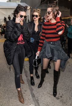 Still in their Anna Sui hair and makeup, Kendall, Gigi, and Bella sport coordinating black and red looks, with Kendall wearing a New World Order logo T-shirt, jeans, brocade puffer, and animal-print boots. (Which is also what she wore to grab a pre-Michael Kors McDonald's with Bella.)