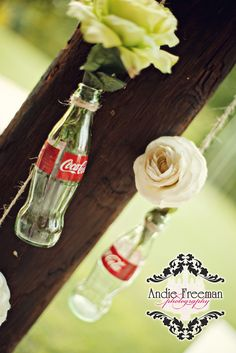Flowers in coke bottles hanging from twine.  Summer shabby chic barn wedding. Photography by Andie Freeman Photography www.TheAthensWeddingPhotographer.com Event design, floral, and planning by Wildflower Event Services www.WildflowerEventServices.com Venue:  Private property in Chickamauga, Ga Barn Wedding Inspiration, Event Services, Private Property, Coke, Event Design, Twine, Wedding Details, Wild Flowers, Real Weddings