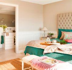 Dormitorio con cabecero en capitoné, ropa de cama verde y rosa, banqueta, arrimadero con molduras y baño en suite