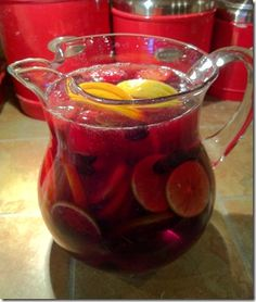 Definitely doing this! Christmas Sangria:  1 lemon 1 lime 1 orange 1/2 cup blueberries (frozen is fine) 1 cup strawberries (frozen is fine) 1 1/2 cups rum 1/2 cup simple syrup (or 1/2 cup sugar) 1 bottle dry red wine 1/2 cup orange concentrate cinnamon for topping the drinks candy cane for stirring