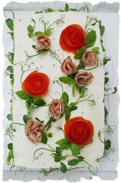 """Voileipäkakun päälle voi valmistaa kauniin ruusun tomaatista. Unelmakakut-kirjassani on kerrottu miten tämä tapahtuu, löydät sieltä paljon myös muita vinkkejä koristeluun ja erityisesti kakkuihin. Pese tomaatit ensin hyvin ja kuori kuorimaveitsellä tomaatin kuorta samalla kiertäen, kunnes kuori on kierretty kokonaan tomaatista. Rullaa pitkä kuoriosa """"rullalle"""", jolloin siitä tulee ruusun näköinen. 1, 5 pkt Oululaisen Reilu- vehnäpaahtoa kakkuun tuli myös 1 leveä kerros ruisvuokaleipää täyte…"""