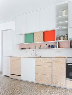 A modern kitchen with cabinets mixing color and plain unstained plywood.
