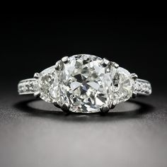 A gorgeous, bright-white and beautiful 3.03 carat antique cushion-cut diamond, of early twentieth-century vintage, has found a fabulous new home between a matched pair of half-moon diamonds, together weighing an additional 1 carat. The scintillating center stone, accompanied by a GIA Diamond Grading Report stating: I color-VS1 clarity, is set almost seamlessly shoulder-to-shoulder with the side stones, creating a continuous flash and sparkle across the finger. Five small diamonds enliven…