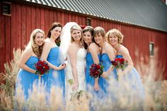 The contrast between the red barn the the blue dresses just makes the bride shine even more.