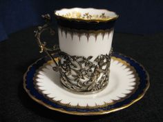 COALPORT DEMITASSE CUP AND SAUCER in a STERLING SILVER HOLDER with CHERUBS