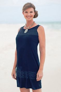 Navy is always a solid color choice! This conservative dress is a knit sheath, featuring tonal crochet insets