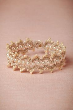"""Prato Bracelet: Exquisite, intricate, and vintage-inspired. L'Orina's signature tatting technique transforms glass pearls into radiant, wearable art. Fastens with a mother-of-pearl button and loop closure. 6""""L, 0.75""""W. Glass pearls, glass beads, cotton and polyester thread. France."""