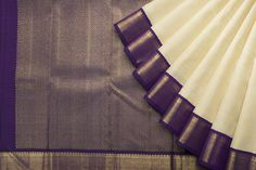 Be a vision in elegance in this cream and purple Kanjivaram with golden pallav.
