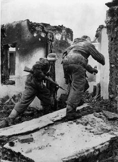 """Füsiliere der Division """"Großdeutschland"""" beim Gegenstoß. Nach einem heftigen Feuerschlag der schweren Waffen dringen die Füsiliere in die zerstörten Häuser ein, um die Sowjets zu werfen und die alte..."""