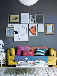 DIY Inspiration- Simple Frames for Your Art Work Make this Amazing Salon Wall!  Love the colour on the wall, works as a perfect backdrop to the bright colours of the sofa and cushions and the artwork of course!