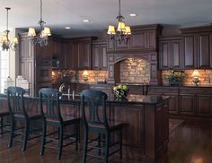 Old World style kitchen with stone backsplash, dark wood floors, dark cabinets, dark countertops. It's a lot dark for me, but I can appreciate the fact that some people want to live in a dim castle. Kind of.