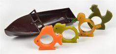 Four vintage bakelite animal napkin rings and a bakelite boat
