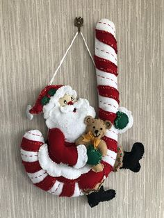 This felt Christmas wall hanging decoration is called Santa With Candy Cane and features Santa Claus on a delicious looking felt candy cane! The decoration is handmade from a Bucilla kit. It has sequins added to the felt which really dazzle the item! It is 13 by 18.5 in size and