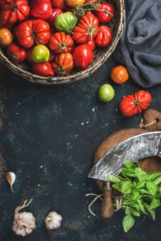 #Colorful ripe heirloom tomatoes  Fresh colorful ripe heirloom tomatoes in basket basil leaves garlic herb chopper knife for cooking over grunge dark plywood background. Top view copy space. Harvest vegetable cooking conception.