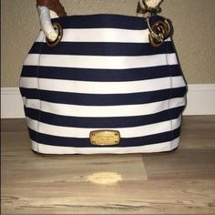 Michael Kors Navy Blue Purse Brand New With Tags!! Super cute for summer!! Good size really spacious. This is the NAVY BLUE tote I have a blacked striped one listed as well. IF YOU FIND THIS BAG CHEAPER SOMEWHERE ELSE PLEASE DONT FEEL THE NEED TO COMMENT ON MY PAGE. Michael Kors Bags