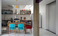 É difícil acreditar, mas onde hoje funciona a charmosa cozinha, antes era a garagem. Com a reforma do escritório Casa 14 Arquitetura, ela ganhou claraboia e armários de concreto aparente. Cadeiras coloridas trazem vida à decoração