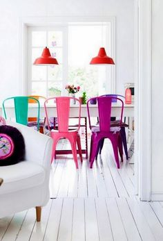 This room is perfection to me – the stark white walls and glossy floorboards serve as the perfect backdrop to these cheerful, colorful Tolix Maraix chairs and metal pendants.