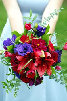 Rustic and natural wedding bouquet of red and purple flowers. Dahlias, roses, lisianthus, tulips, and fresh greenery.