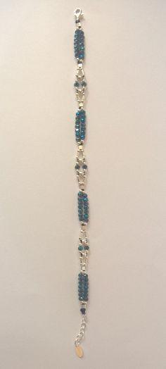 Bracelet conçu et réalisé par mes soins entièrement à la main. Tissage de petites perles dargent 925 et de swarovski bleu foncé (2 à 3 mm) sur cordon de soie/polyester bleu foncé, résistant à leau, (déconseillé en piscine chlorée : risque de décoloration). Finitions soignées