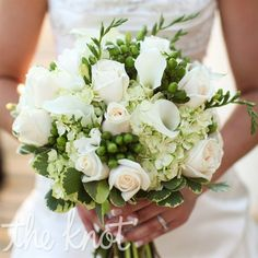 This has several floral items that you like including freesia (the green buds that open to white flowers but have some green unopened buds that line up and look elegant. It also has roses, calla lilies, hydrangeas, h. berries, and green and white foliage