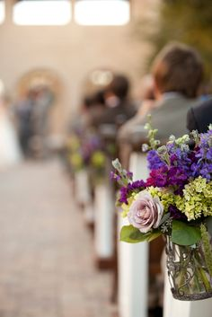 Posted from Floral Occasions, our wedding florist based out of San Juan Capistrano. This picture was taken at our venue Serra Plaza! Flowers: purples, fuchsia, lavenders, beer hops, and more! The flowers lined church pews along the aisle.