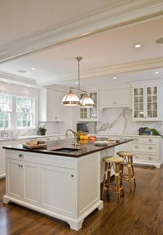 Chic kitchen features white cabinets painted Benjamin Moore Super White paired with Absolute Black Granite ocuntertops and a statuary marble slab backsplash.