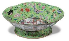 """A """"CANTON FAMILLE ROSE"""" LIME-GREEN GROUND CENTERPIECE  SECOND QUARTER 19TH CENTURY  Of quatrefoil form, the interior and sides enameled with cartouches of court figures and ladies in gardens and pavilions, surrounded by floral sprigs and butterflies, the underside with a six-character Daoguang seal mark 6k"""