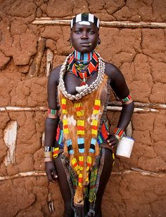The Hamars are a people of East Africa living in southwestern Ethiopia in a fertile area of the Omo Valley. The traditional dress code for unmarried Hamar girls includes elegant cowrie-shell collars, seeded or glass-beaded necklaces, and decorated goatskin clothing, Ethiopia.