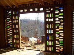 Entrada de un Blog sobre construcción circular con sacos de tierra. Pero trae esta foto de la entrada a la casita: una configuración luminosa y sencilla de botellas para la entrada.