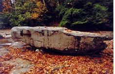 """Boggs Mill Stone - Located along Webster County Route 1 and the Little Kanawha River is a large rock that Andrew """"Andy"""" Boggs reportedly moved from the Lewis County side of the Little Kanawha River to his mill site in the late 1800s. Boggs was a gunsmith and is also remembered throughout the area for his extraordinary physical strength. Boggs was the first to be buried on top of a hill east of the millstone. The cemetery is known as the Boggs Cemetery. The story is told that during the Civil…"""