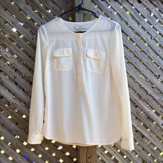LOFT Cream Blouse 1/2 button down cream blouse. 2 front pockets. Long Sleeve. Very soft like a cotton but somehow 100% polyester. True to size otherwise I'd keep it! Clean, always gently laundered and line dried. LOFT Tops Blouses