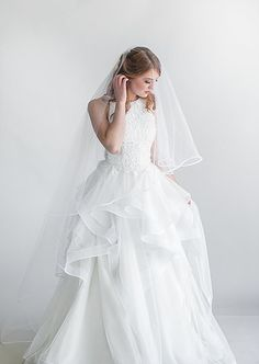 Peony motif corded lace ballgown with tiered English net and horsehair skirt. Back corset and crushed velvet ribbon detail.