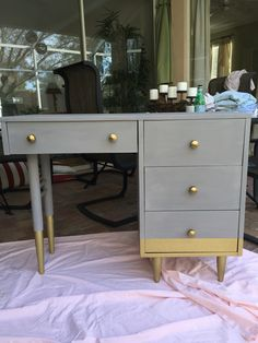 DIY chalk paint desk! Grey Amy Howard one step paint (Annie Sloan-like). Gold dipped legs with krylon 18k gold spray paint. Anthro hardware.