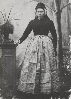 Vrouw in Terschellinger streekdracht. De vrouw is gekleed in de zondagse dracht van Oost-Terschelling. Ze draagt een effen groen jak en Tibet rok en een bont schort. Op het hoofd draagt ze de 'driestrooksmuts', met daarover de zwarte kap. Om de hals een bloedkoralen snoer met gouden slot. ca 1895 #Terschelling
