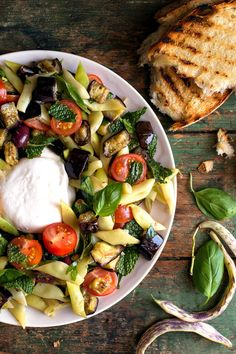 Although burrata is inarguably the star of this stunning summery salad, roasted eggplant, cherry tomatoes and Romano beans add a brilliant mix of colors, textures and flavors to the creamy mozzarella. (Photo: Andrew Scrivani for The New York Times)