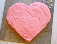How to make a heart shaped cake THE EASY WAY: 1 square cake, 1 round cake. Cut round cake in half to make the top part. Set square cake on a angle. Put round halves against the two top sides of the square cake. FROST! Happy Valentine's Day!