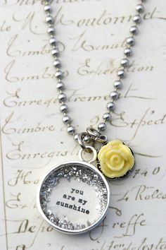 "18mm (about 3/4"") hand glittered charm that reads ""you are my sunshine"" 16"" silver ballchain - lead and nickel free.  Makes a special gift a little girl will treasure. Handmade in the USA"