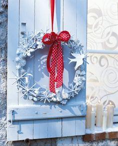 Couronne de Noël faite avec des graines et morceaux de bois peints en blanc et ornée d'un ruban rouge à pois