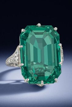 An Art Deco emerald single-stone ring, circa 1920. The large cut-cornered step-cut emerald, weighing 14.70 carats, within a gallery decorated with rose-cut diamonds, between shoulders set with old brilliant, single and rose-cut diamonds, mounted in platinum, French assay mark. #ArtDeco #ring