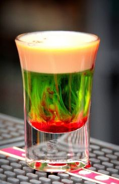 Fallen Froggie  0.5oz Midori 0.5oz Baileys Splash of grenadine  Mix equal parts and drink up!