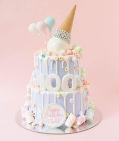 Tiered cake in pastel colors with an upside down dripping ice cream cone and balloon cake toppers // Beautiful wedding cake inspiration