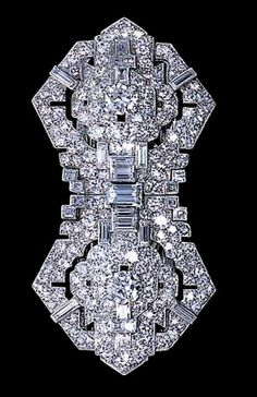 A DIAMOND DOUBLE CLIP BROOCH, BY CARTIER Each clip designed as a pavé-set and baguette-cut diamond pierced stylised shield-shaped panel to the circular-cut diamond centre, circa 1926, with French assay marks Each clip and frame signed by Cartier, Paris