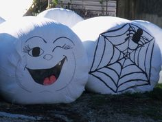 Round Hay Bales wrapped with white plastic and then painted on.