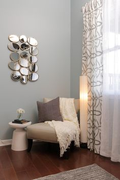 BEDROOM, AFTER: Mirror art reflects light and makes the space feel bigger which is perfect for a basement guest bedroom. A seating area is a great extra for a guest room if you have the space.