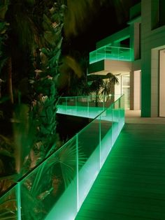 The LED lighting scheme continues outside of the building, where lighting strips color the decks and walkways with glowing glass balustrades...