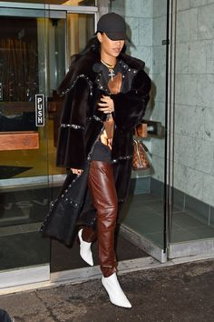 Throwback time: Rih pairs a vintage D&G riveted leather coat with Céline's optic white Rodeo boots and a Louis Vuitton handbag. Note the yellow sapphire and diamond choker worn over an R Kelly T-shirt: the perfect summation of her hi-lo style.