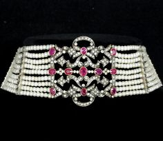 Edwardian Choker Necklace featuring over 6 carats of beautiful oval cut red rubies, over 7 carats of diamonds, and small natural pearls. 18k Yellow Gold and Silver. The 11 oval cut red rubies are bezel set in yellow gold and featured in the center piece. The entire centerpiece is also encrusted with 154 diamonds.