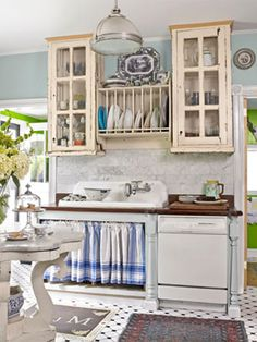 To make this formerly modern kitchen look vintage, the owner hung custom cupboards above a vintage basin, installed a teakwood countertop around the sink, and added a marble backsplash.